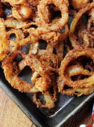 homemade onion rings piled on baking sheet