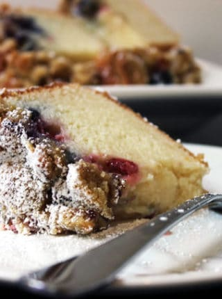 Sweet & Tangy Triple Berry Sour Cream Crumb Cake with Slivered Almonds. A delicious summer treat with the ripest sweetest fruit. The cake is tangy from the sour cream, sweet from the berries and crispy from the topping.