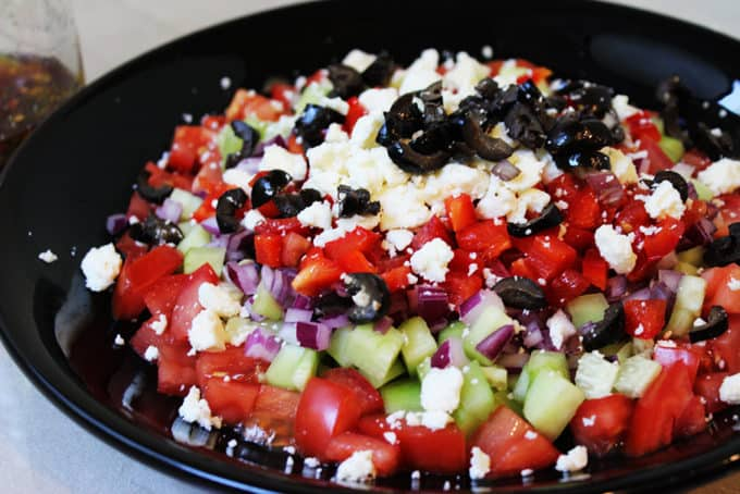 A delicious Greek Vegetable salad in a rainbow of colors. Fresh and healthy it is topped with salty rich feta and kalamata olives. Less than 200 calories a serving, eat the rainbow!
