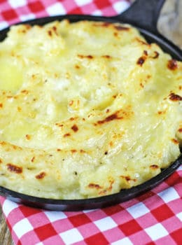 The richest mashed potatoes with five kinds of dairy! They are tangy, cheesy, rich and creamy with a deliciousy crisp crust out of the oven.