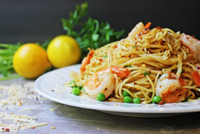 Shrimp Scampi Pasta heaped on plate with peas and parmesan