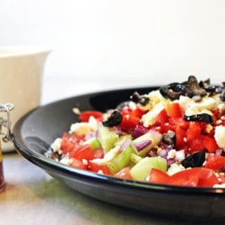 A delicious Rainbow Greek Vegetable salad in a rainbow of colors. Fresh and healthy it is topped with salty rich feta and kalamata olives. Less than 200 calories a serving, eat the rainbow!