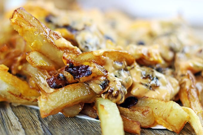 Animal-Style French Fries are fried golden brown, topped with melty American Cheese, buttery melted caramelized onions and a signature fry sauce. Serve with a fork or eat with your fingers if you dare, these fries are a cult favorite!