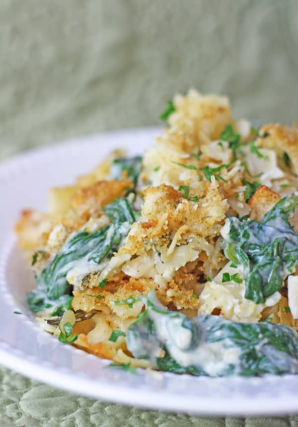 Your favorite Spinach and Artichoke Dip in a pasta bake with a Parmesan Buttery Cracker crust! Made with Mozzarella, Parmesan, cream cheese and sour cream with fresh spinach and artichoke hearts.
