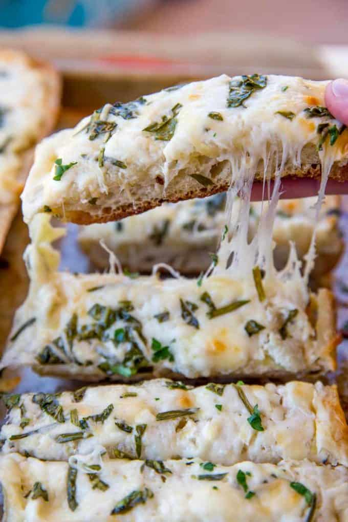 Spinach Artichoke Dip Cheesy Bread is two of your favorite appetizers in one. Cheesy garlic bread meets spinach and artichoke dip in just 30 minutes!