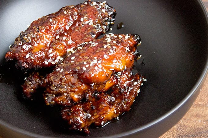 Sticky Asian chicken wings topped with sesame seeds in skillet