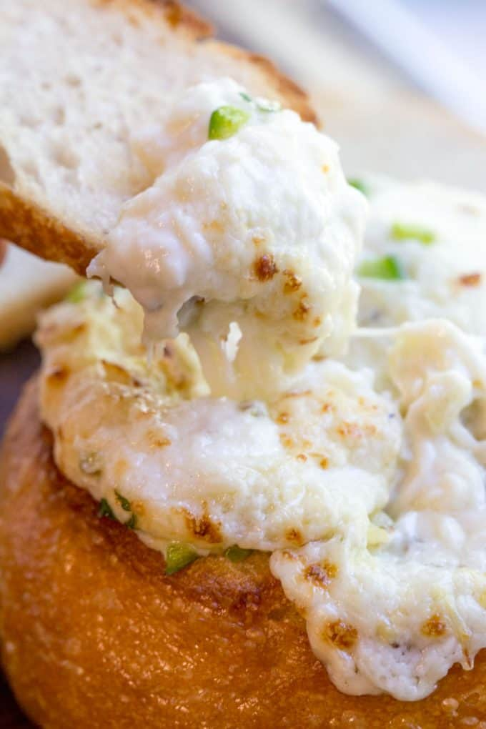 Artichoke Cheese Dip takes five minutes of prep and full of artichokes, Parmesan and cream cheese that is baked in a bread bowl for the perfect appetizer! dinnerthendessert.com