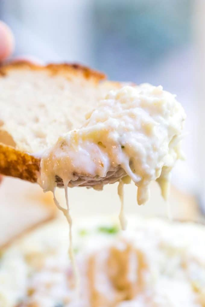 Creamy artichoke dip on crusty piece of bread