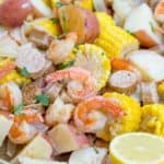 Easy Shrimp Boil recipe with andouille sausage, corn and potatoes is the perfect summer recipe to enjoy the last few weeks of summer before life goes back to normal and most meals aren't served on giant trays and newspaper.