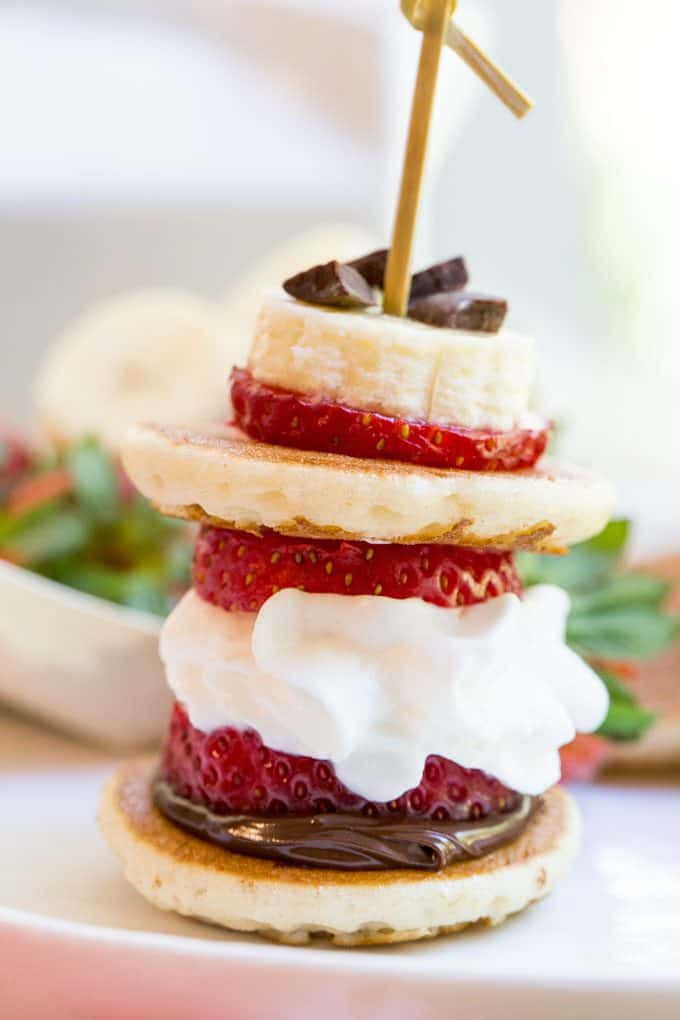 Banana Split Pancake Bites are an easy brunch dish for a party or for your little ones with homemade silver dollar pancakes, Nutella, bananas, strawberries, whipped cream and chocolate chips.