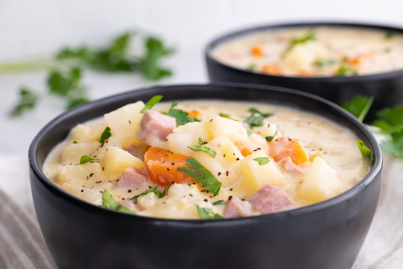 Slow Cooker Ham and Potato Soup in bowls with parsley garnish