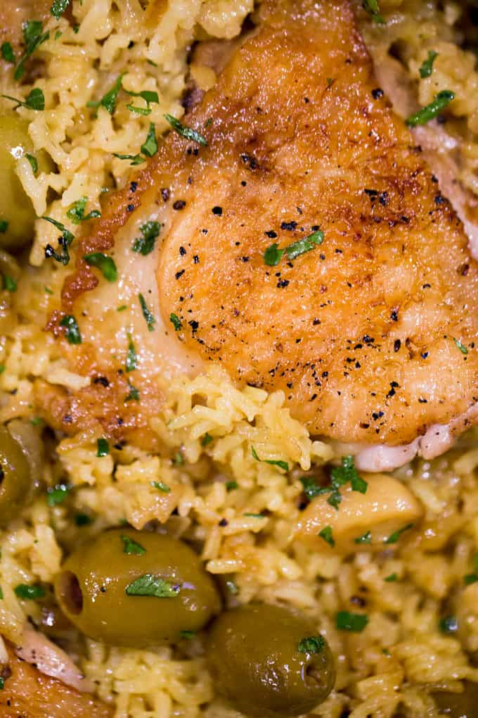 Spanish Olives Chicken and Rice made in a single cast iron skillet is a gorgeous meal made easy with delicious Spanish queen green olives, caramelized onions, garlic and saffron rice.