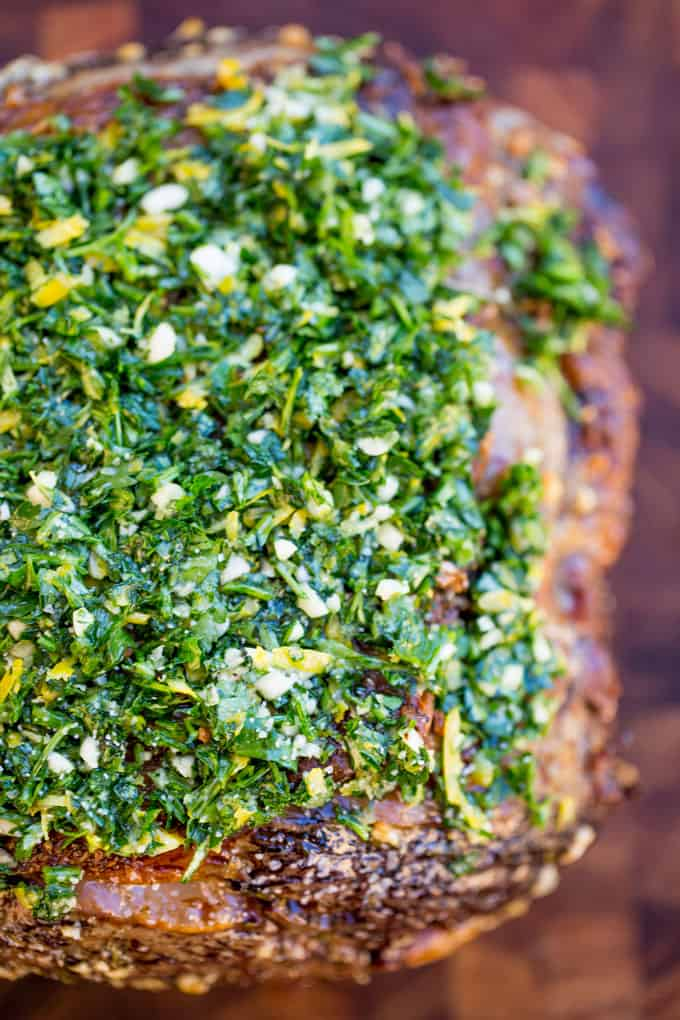 Perfect Garlic Prime Rib made with a garlic, thyme and rosemary crust is gorgeously browned on the outside and a perfect medium on the inside. Topped off with a gremolata it is the perfect show-stopping holiday/event meal!