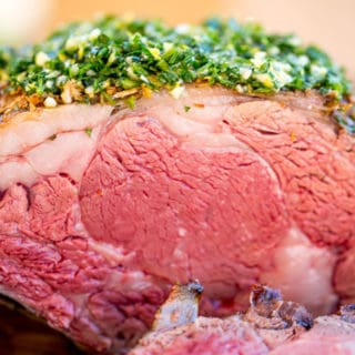 Perfect Garlic Prime Rib made with a garlic, thyme and rosemary crust is gorgeously browned on the outside and a perfect medium on the inside. Topped of with a gremolata it is the perfect show-stopping holiday/event meal!