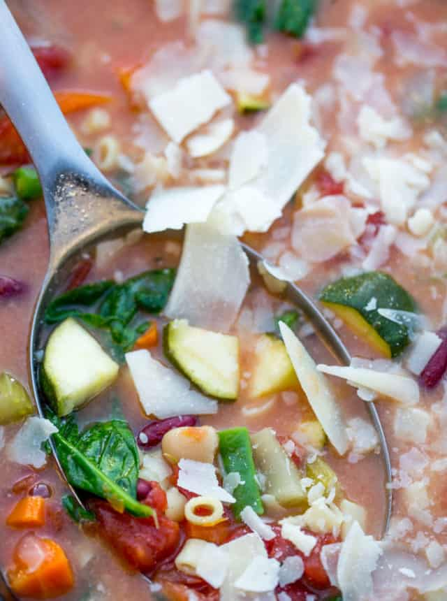 minestrone soup in ladle with fresh parmesan cheese on top