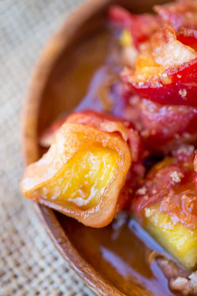 Spicy Sweet Bacon Wrapped Pineapple Bites caramelized with brown sugar and hot sauce make a perfect sticky, sweet, spicy, fruity bacon bite your guest will love in just minutes!