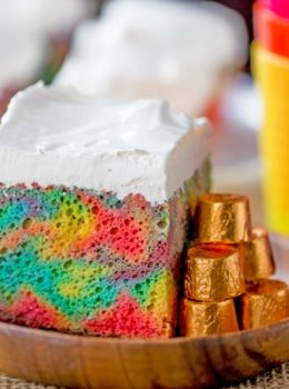 Rainbow Poke Cake With Whipped Cream made with no cake mix. Condensed milk makes this poke cake super moist and fluffy stabilized whipped cream won't melt!