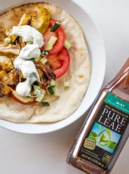 Chicken Shawarma Pita Wraps with Dill Yogurt Sauce are baked on a sheet pan with sweet red onions and wrapped in a pita for the ultimate lunch without the long lines at your favorite lunch restaurant.