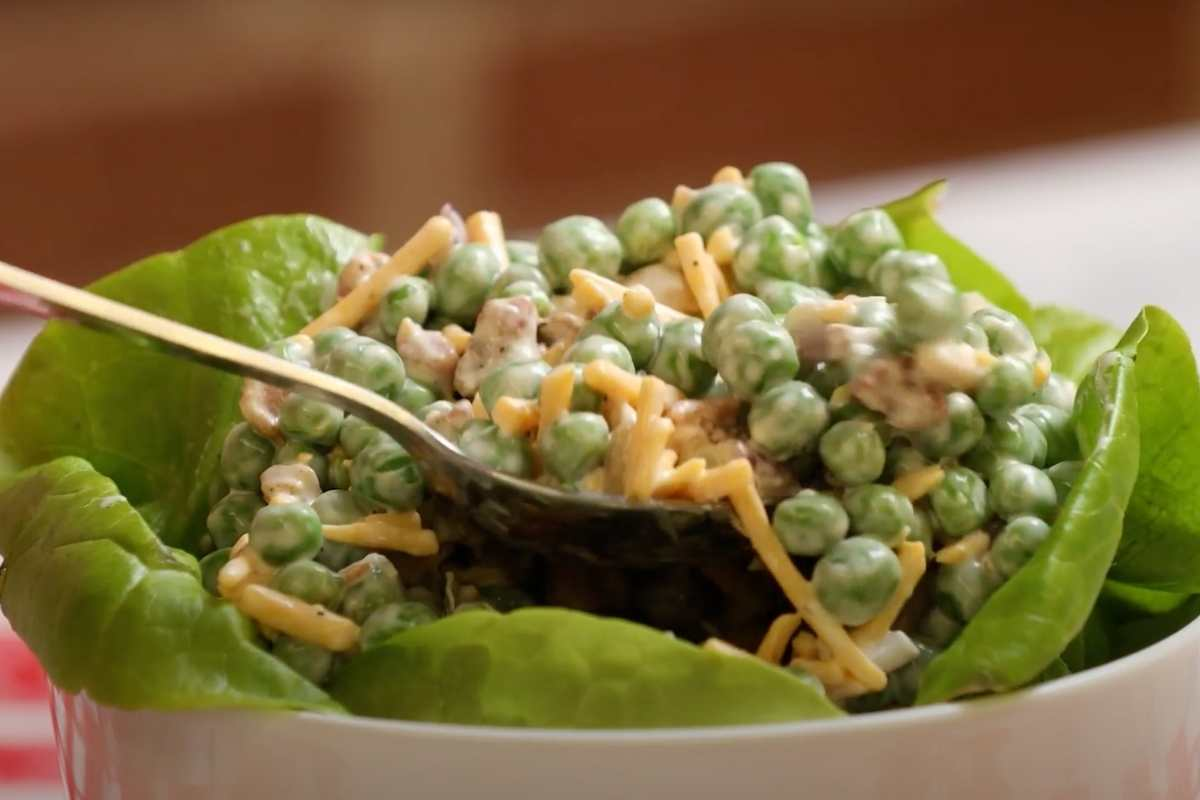 Creamy Bacon Pea Salad on bed of lettuce with spoon