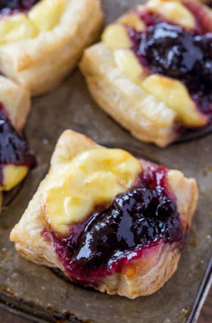 Cheesy Puff Pastry Bites with blueberry jam and goat cheese.