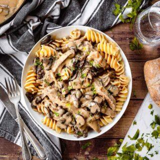 Beef Stroganoff steak with creamy mushroom gravy over egg pasta in bowl