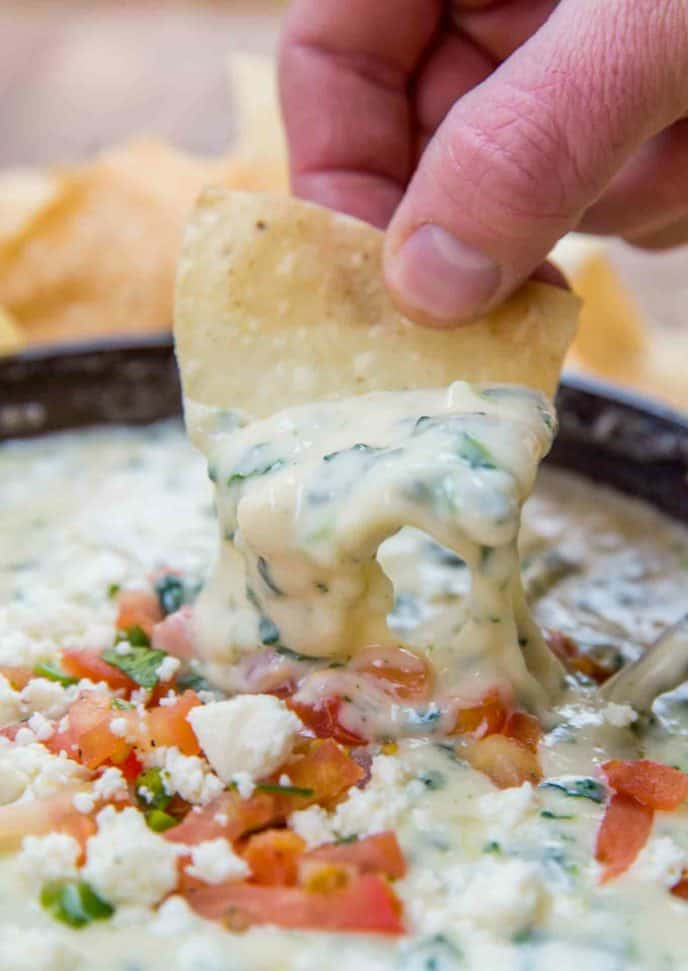 Chip with cheesy melted spinach queso