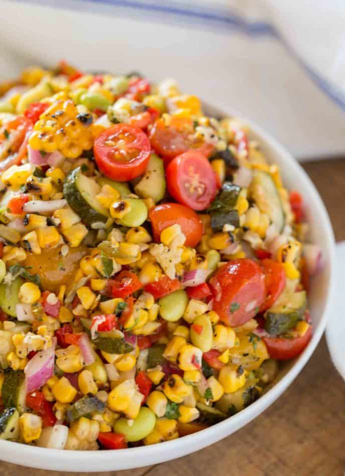 Corn Succotash is the perfect summer side dish made with freshly grilled corn, zucchini, grape tomatoes, red bell peppers, lima beans and red onion. | #summer #sides #sidedish #picnic #dinnerthendessert #easysidedish #vegetarian #corn