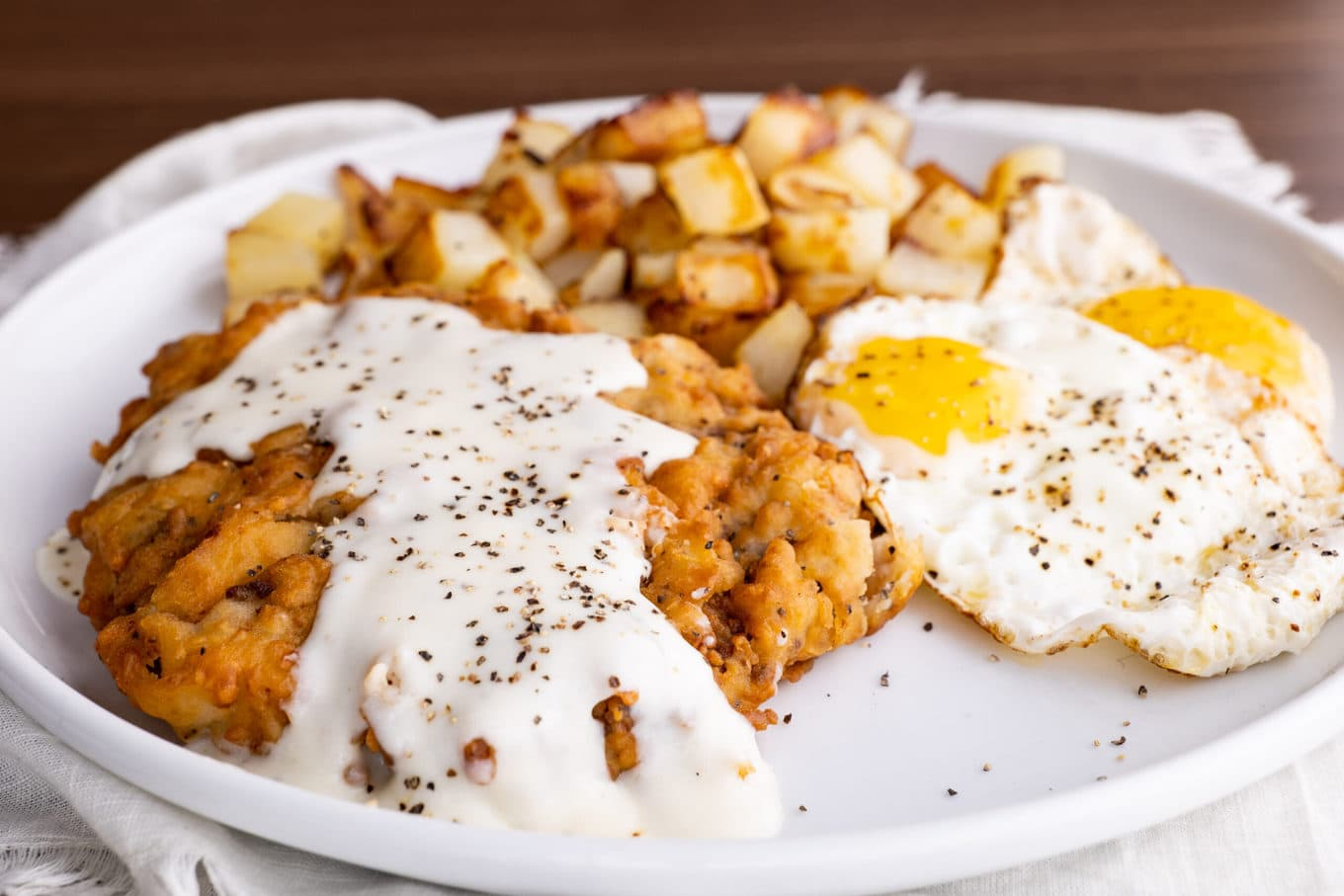 Chicken Fried Steak on plate with eggs and hash browns