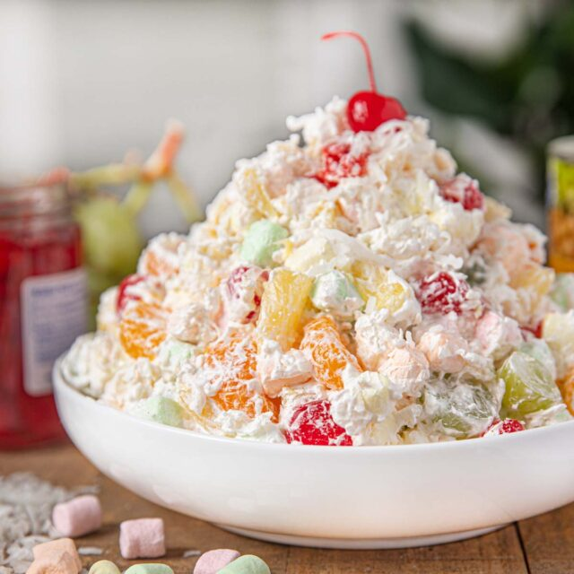 Ambrosia Salad in White bowl with fruit and marshmallows on table