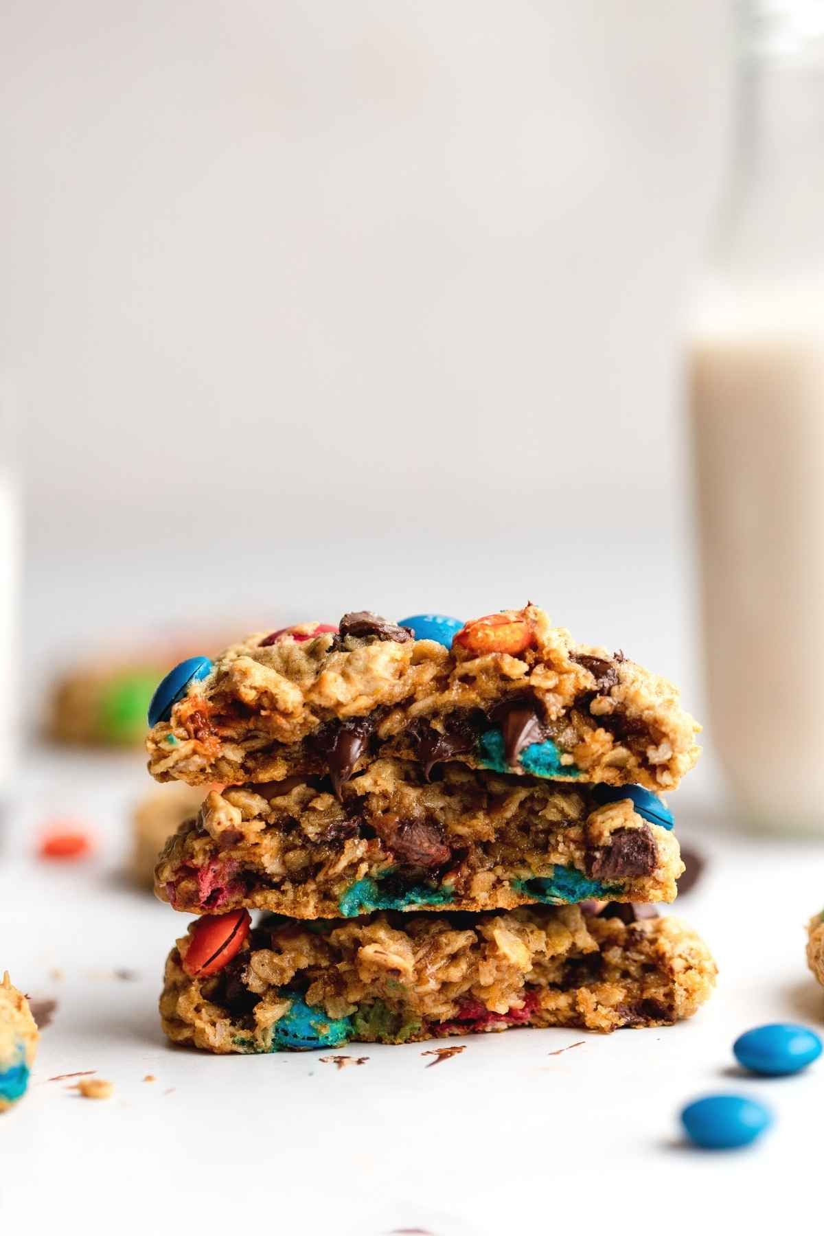 Monster Cookies stacked on table with glass of milk