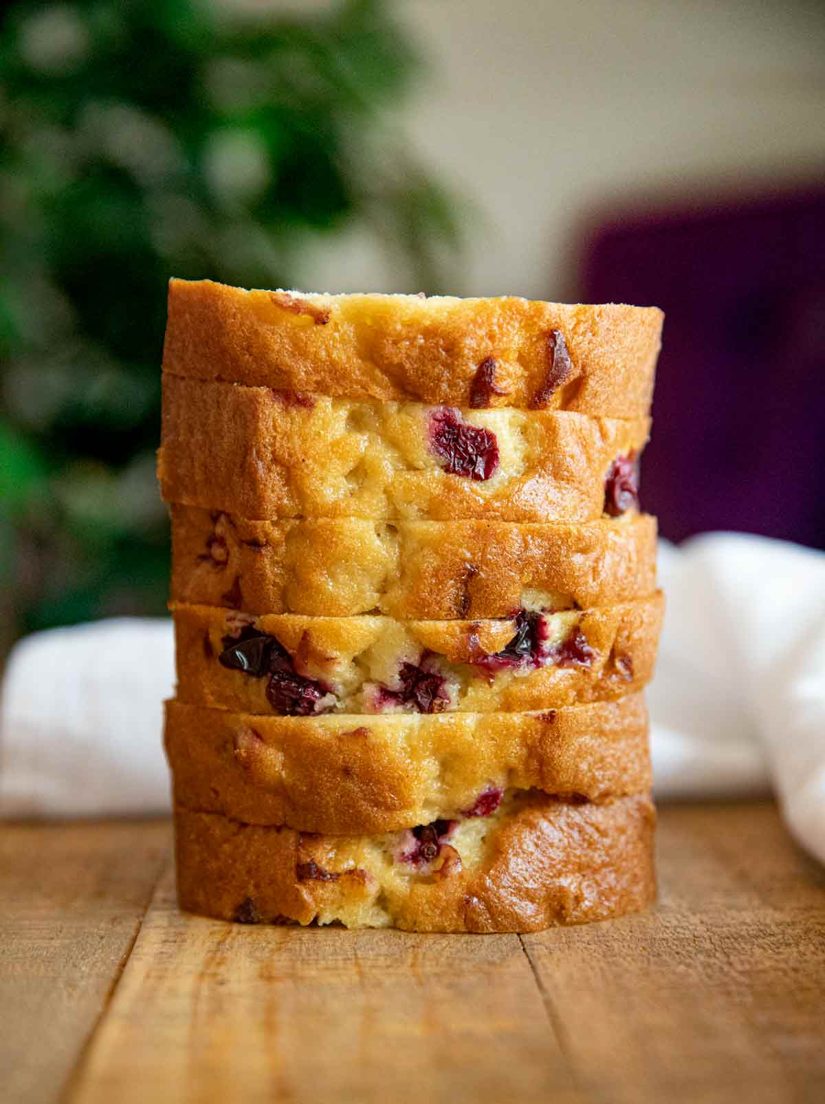 Stack of cranberry bread slices on wooden table