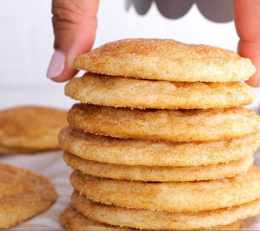 Snickerdoodle Cookies stacked with hand placing