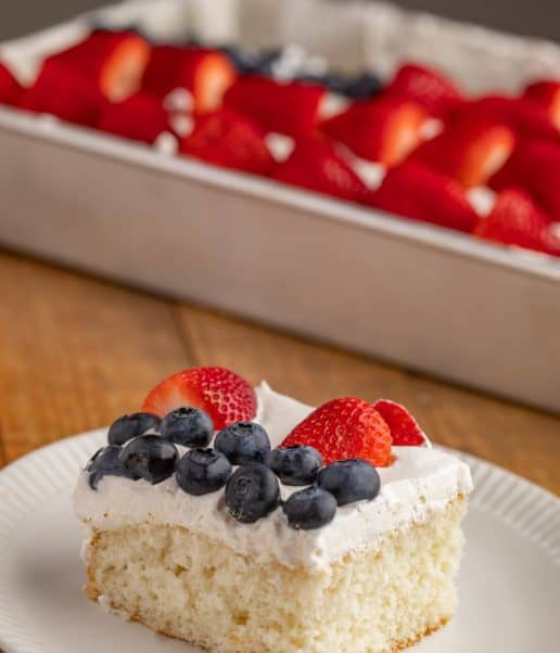 Slice of white cake with strawberries and blueberries