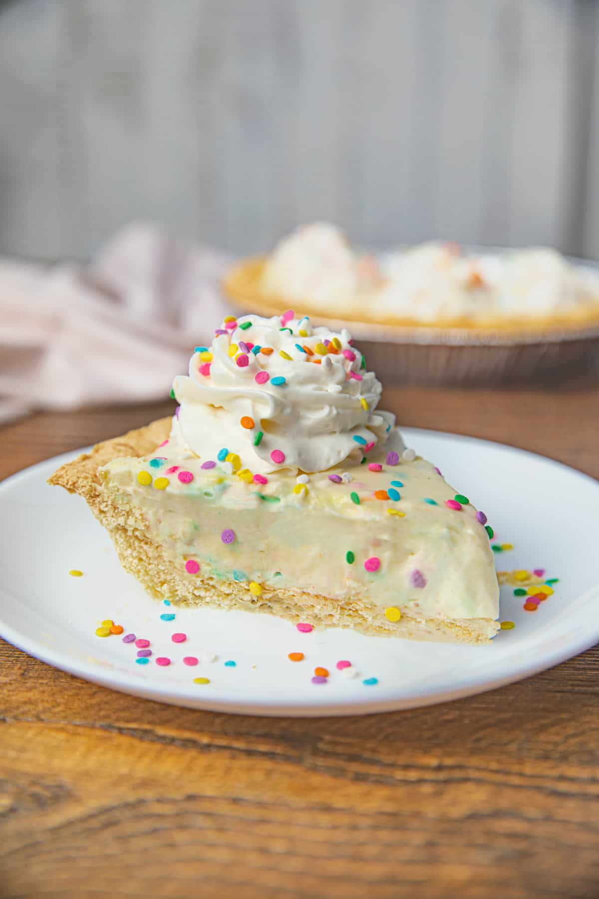 Slice of Birthday Cake Pie with Whipped Cream and Rainbow Sprinkles