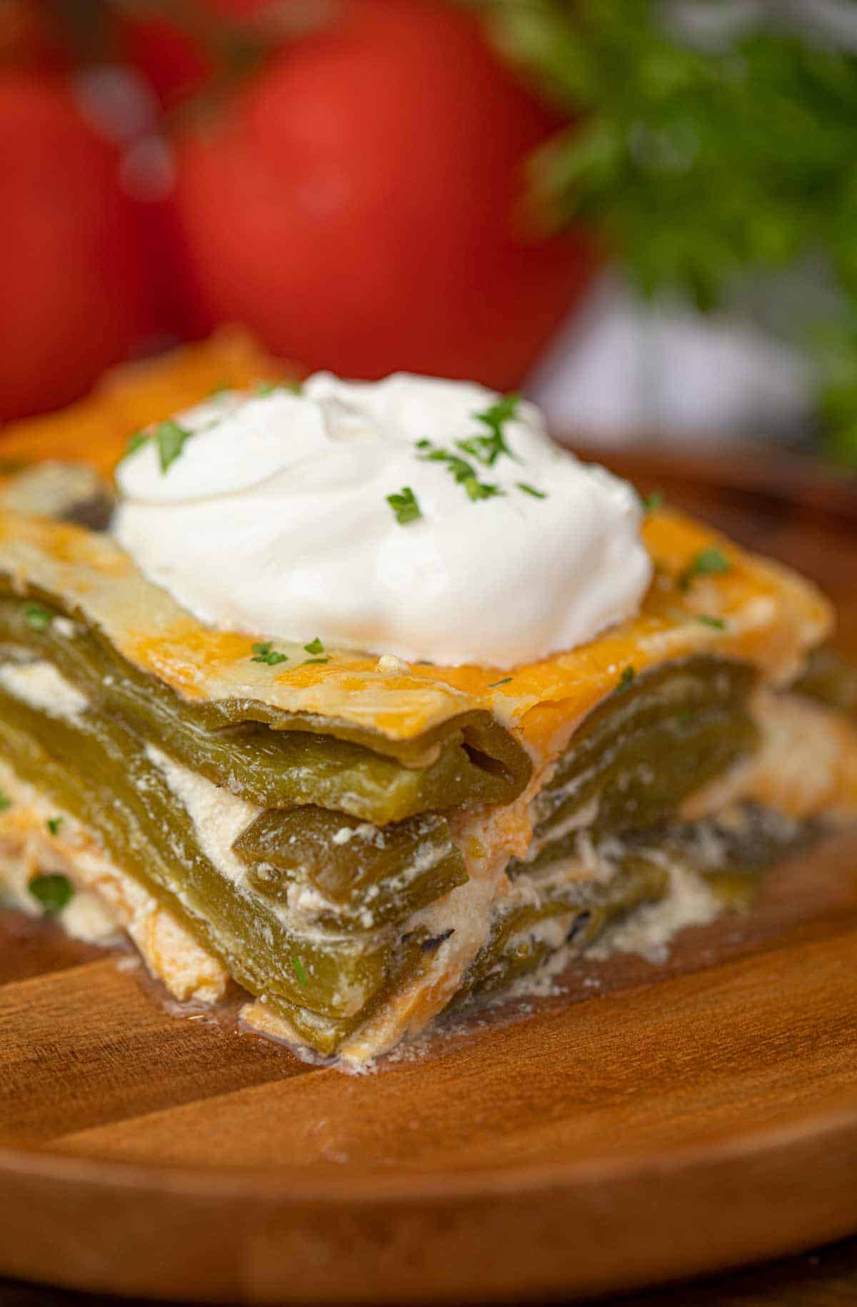 Slice of Chile Relleno Casserole with Green Chiles, Cheddar Cheese and Sour Cream on Wooden Plate