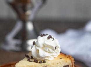 Slice of Chocolate Chip Cheesecake with Whipped Cream on plate