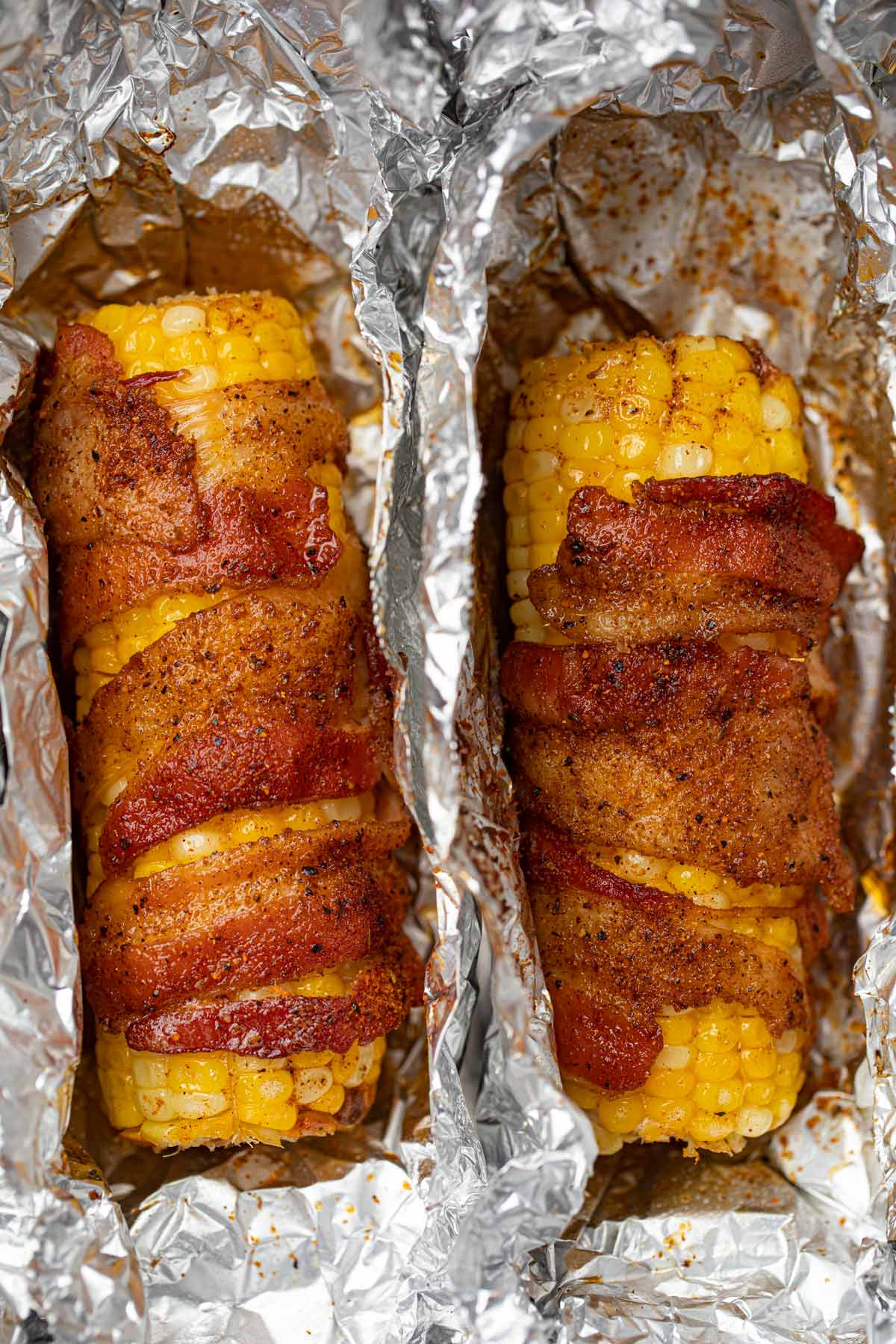 Two bacon wrapped corn on the cobs
