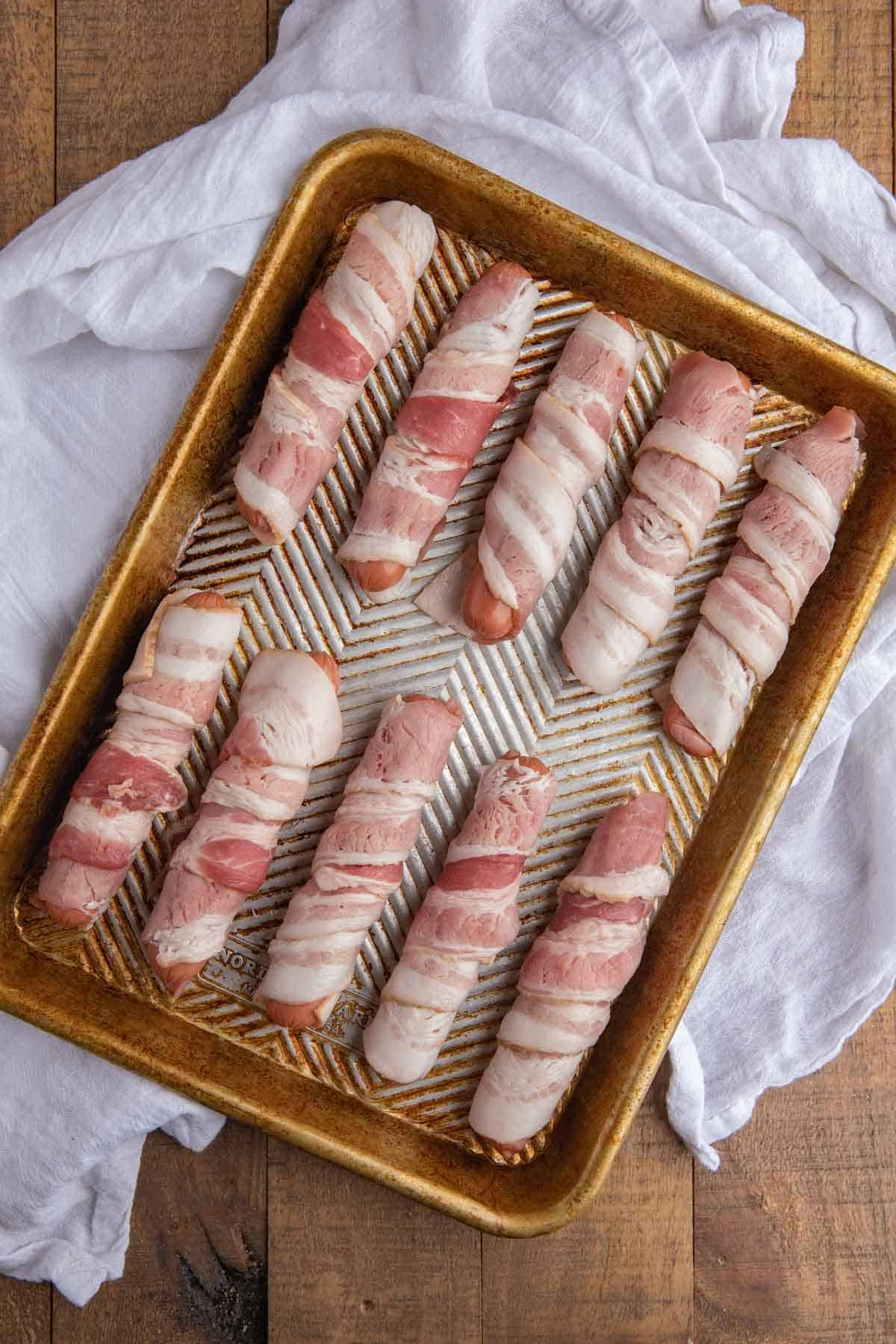 Raw Bacon wrapped around hot dogs