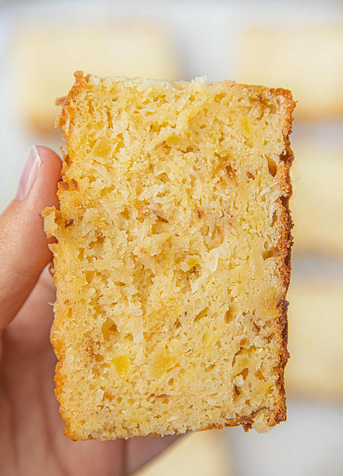 Hand holding slice of Pineapple Coconut Bread
