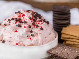 Peppermint Bark Dip topped with mini chocolate chips and peppermint candies