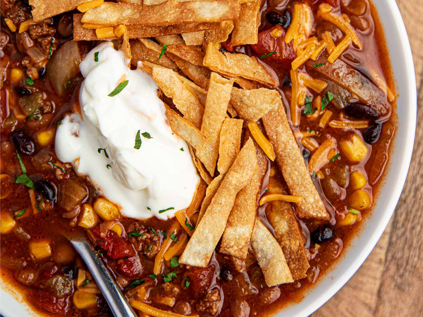 Bowl of Ground Beef Taco Soup made in slow cooker in a white bowl with sour cream and cheese and chips