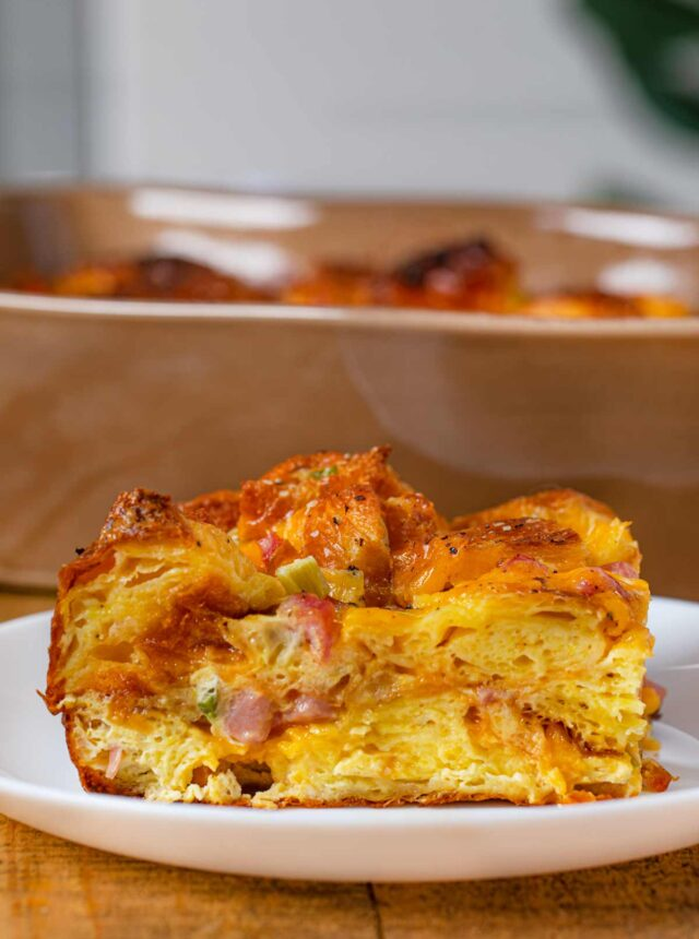 Slice of Ham Cheese and Egg Croissant Casserole on small white plate