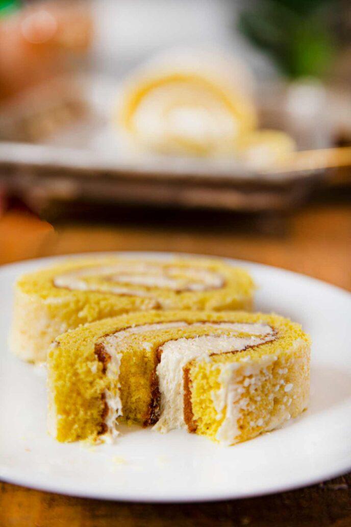 Bite out of slice of lemon cake roll on white plate