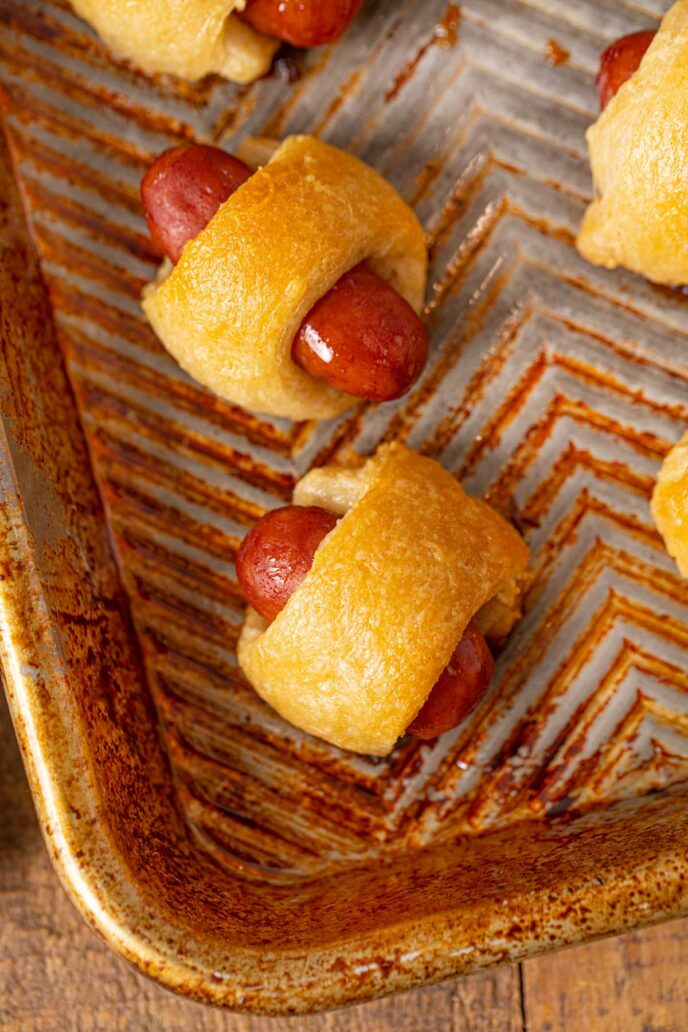 Mini Beef Smokie Wrapped in crescent dough to make a pig in a blanket on a metal tray