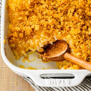 Funeral Potatoes in baking dish with serving spoon
