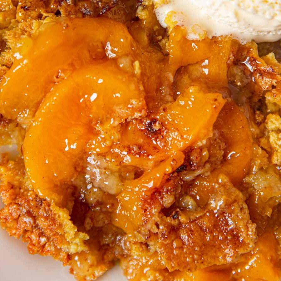 Peach Crisp serving on plate with vanilla ice cream