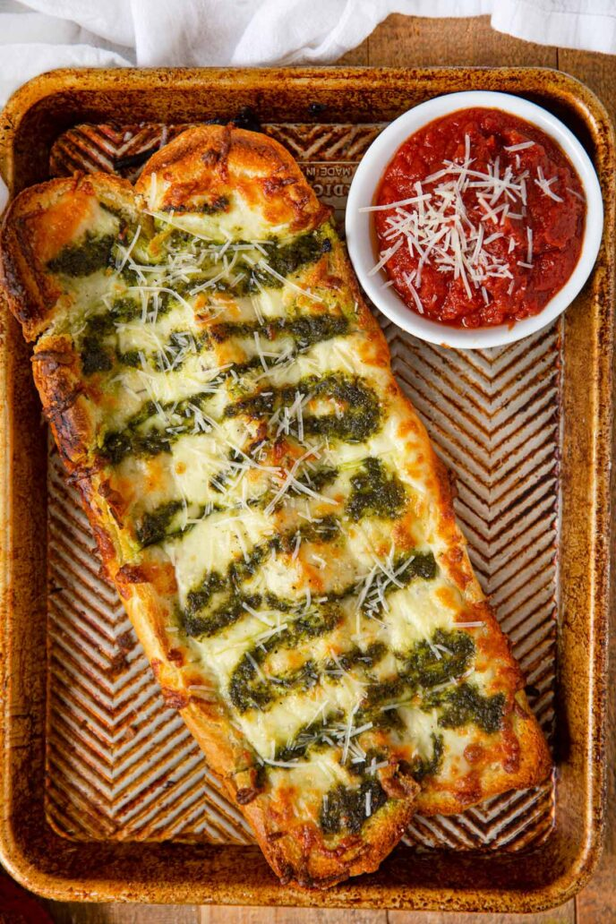 Pesto Cheesy Bread on baking sheet with dipping sauce
