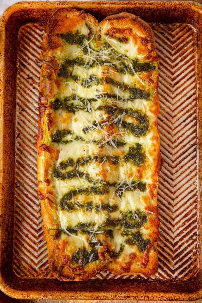Cheesy Pesto Garlic Bread on baking dish