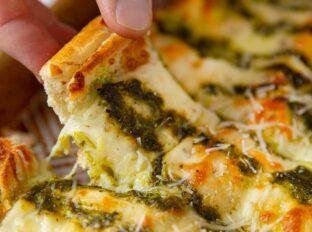 Pesto Cheesy Bread picked up slice