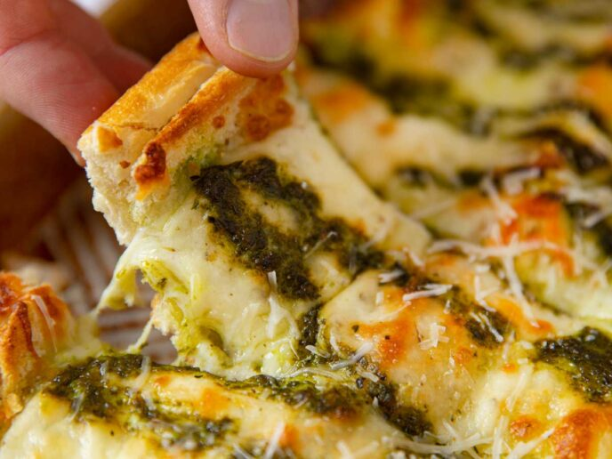 Pesto Cheesy Bread picked up slice